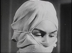 A woman wears a surgical mask and headcloth exposingonly her eyes..