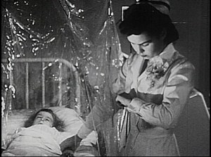 A nurse reaches into a plastic enclosure to take the pulse of a young patient.