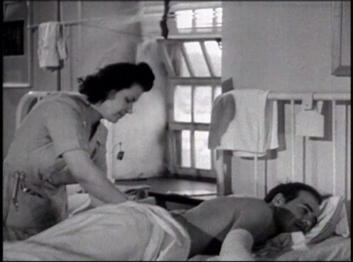 A woman in a nurses uniform treats a male patient lying on his face in a hospital bed.