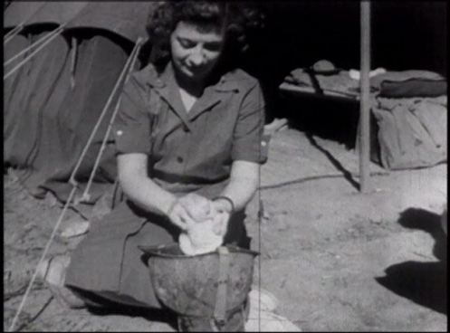 A woman in uniform washes something using an army helpmet as a basin outside a tent.