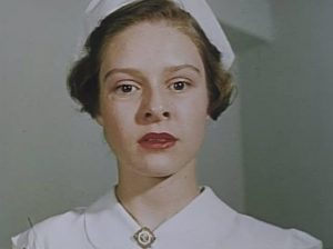 A young woman in a Nursing uniform looks concerned.