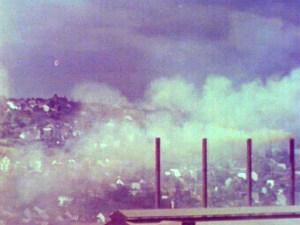 Smokestacks fill the air over a hillside town.