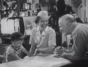 A woman in a nursing uniform sits smiling with an old man and a boy.