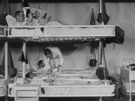 A sailor moves between rows of hanging cots stacked two high.