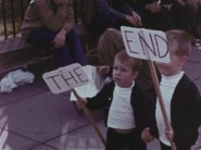little kids holding two signs; one says THE and the other says END