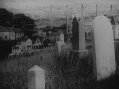 a view of a graveyard looking over a a few houses in the background