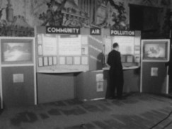 a poster area with papers that has a sign on top that reads Community Air Pollution