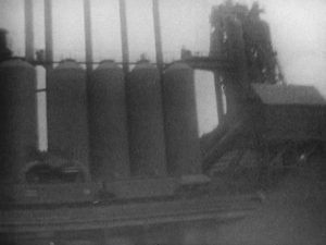 4 large cylindrical tanks standing parallel to each other, next to some machinery