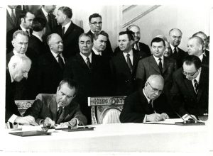 Men sit at a table signing documents while many other men in suits stand behind them.