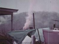 Smoke coming out behind a green tarp