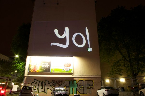 "Image of a large will with a projected ""Yo"" on it from Graffiti Research Lab"