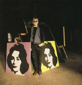photo of Andy Warhol with some of his paintings of Elizabeth Taylor