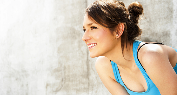 young woman resting after run by the wall in city with big smile. in blue sportswear.