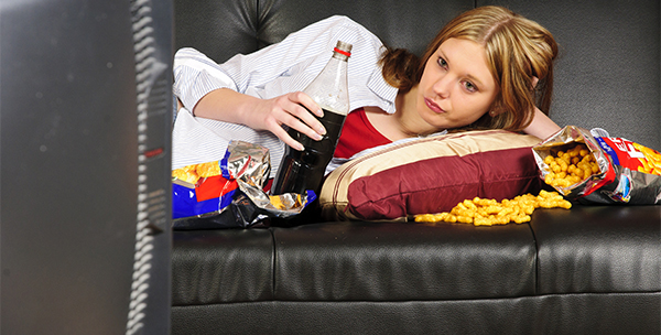A young woman, teenager with long blond hair lolls on a black leather sofa, watching television and eating crisps and coke here.