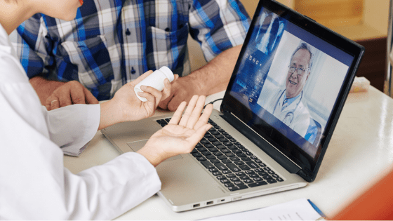 5 Tips on Transitioning to Telemedicine - Doctor on screen on laptop tasing to patient holding medicine in hand
