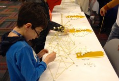 """Liam Gallup, 10, of Rogers Park, tries to build the """"tallest and widest"""" noodle and marshmallow creation at the Project Exploration booth."""