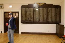 Knudston checks out a dedicated space for the oldest memorabilia in Post 414's building. Behind him is a memorial to the men and women of Forest Park, who served in the armed forces during WWII.