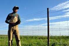 Mike Saxton, a restoration technician at Nachusa, explains the work that went into creating this 6-foot, high-tensile electric fence. Volunteers and workers at Nachusa spent the entire summer in 2014 constructing and placing the fence; each post is actually old oil field piping from Mississippi that the crew cut down and repurposed to create the fence.