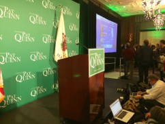 Black retractable tape barriers divided the room in thirds. The front was for the stage and photographers, the middle was for supporters of Quinn, and the back was for reporters.