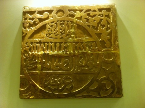 Image of A slab on which the name of the Mamluki Sultan al-Ashraf Qa'it Bey is inscribed. The inscription is inside a disc which in turn is surrounded by interlaced floral patterns.