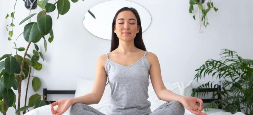 how to create a meditation room woman meditating in bedroom