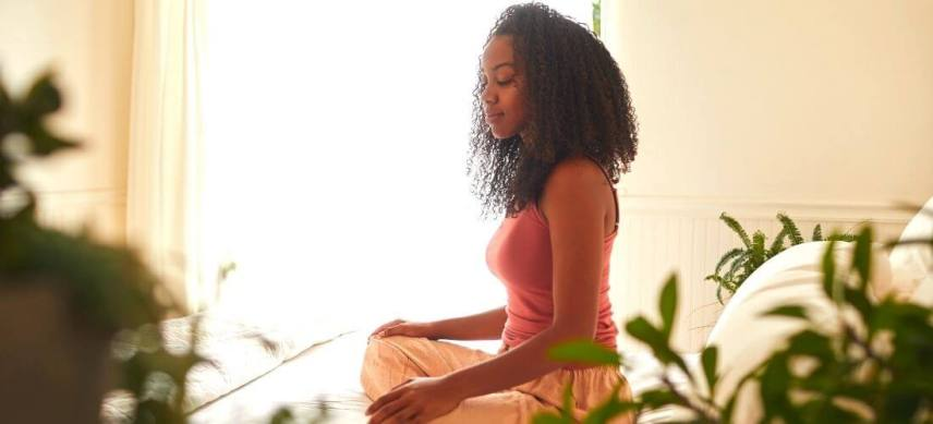 meditation tips for beginners woman meditaitng on top of bed