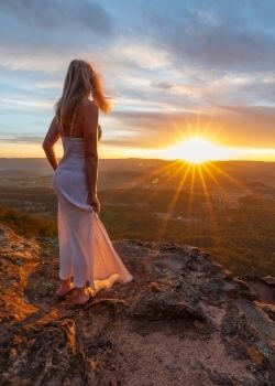 woman looking at sunset to improve herself