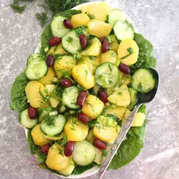 A platter of potato salad, decorated with dill over a bed of green lettuce