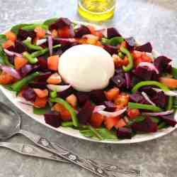 An oval platter with a beets salad with burrata in the middle. Serving utensils are in front of the platter and an olive oil dispenser is on the back.