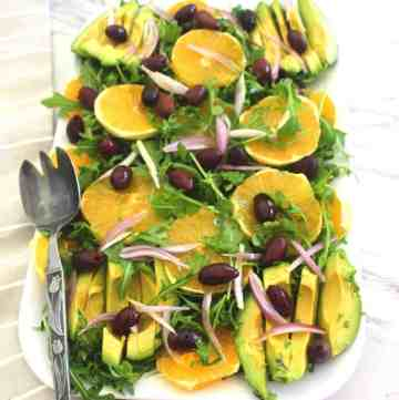 Winter orange salad with kalamata olives, arugula and avocado. This delicious Mediterranean salad is served with a citrus dressing.