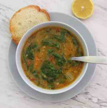 Instant Pot cooked yellow split peas soup with spinach, shown served in a soup bowl with bread and lemon