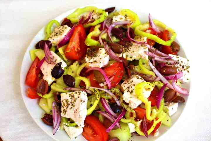 Greek Salad made with cucumbers, tomatoes, black olives, feta cheese, red onions. This is usually called Sallate Fshati in the neighboring country of Albania.