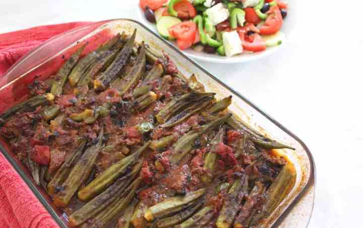 Baking dish just out of the oven with Mediterranean Baked Okra (Tave me Bamje) served with Greek Salad.