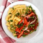 Bolivian Picante de Pollo - Chicken in Spicy Sauce served with fresh tomato, onion, peas and pasta