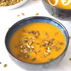 Leek soup with butternut squash and potatoes cooked in a pressure cooker, soup is garnished with pumpkin seeds. The other bowl of soup in the background is garnished with cream.