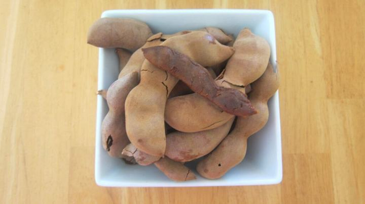 A bowl full of tamarind fruits. I peeled one so you can see how it looks inside.