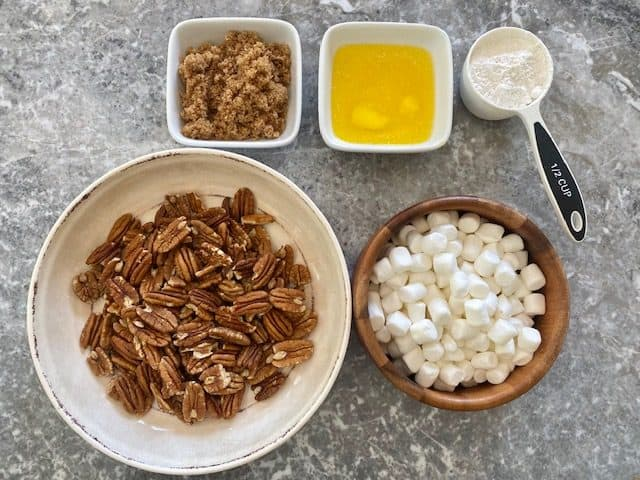 Ingredients for topping are layed out, pecans, marshmallows, butter, brown sugar and flour.