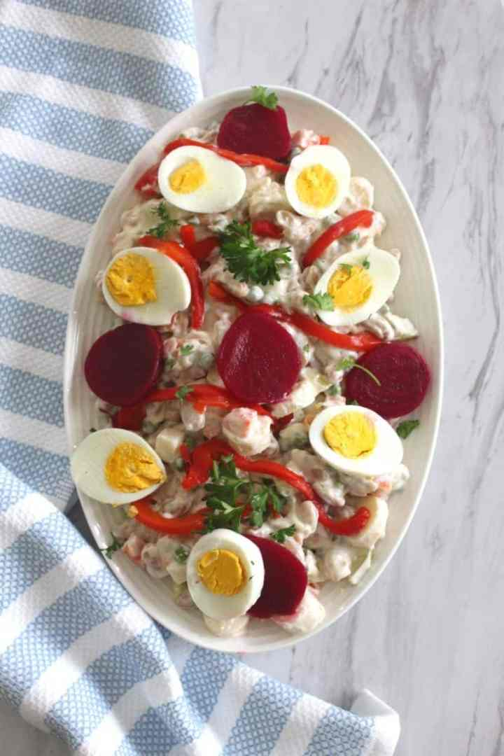 Albanian New Year's Eve Russian Salad - side dish showing a russian salad garnished with beets, eggs, roasted red peppers and parsley.