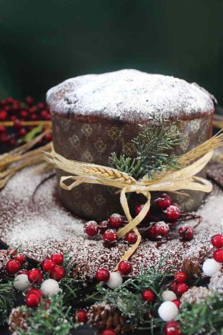Homemade Chocolate Chips Panettone shown in a festive & colorful setting. Panettone is covered in confectioner's sugar