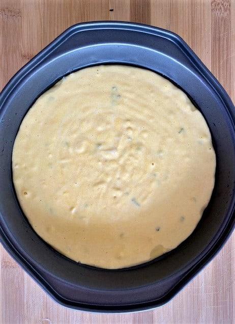 Cornbread dough ready to bake, shown in baking dish.