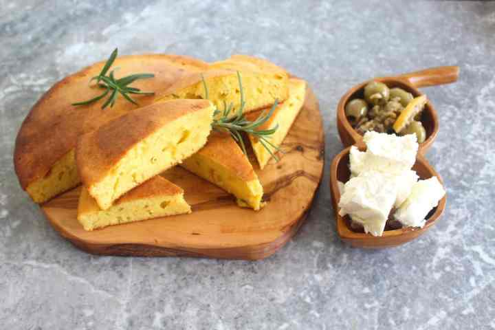 Rosemary cornbread is served sliced on a wood board and decorated with rosemary twigs. Next to it there are two wooden round bowls filled with chunks of feta cheese and olives.
