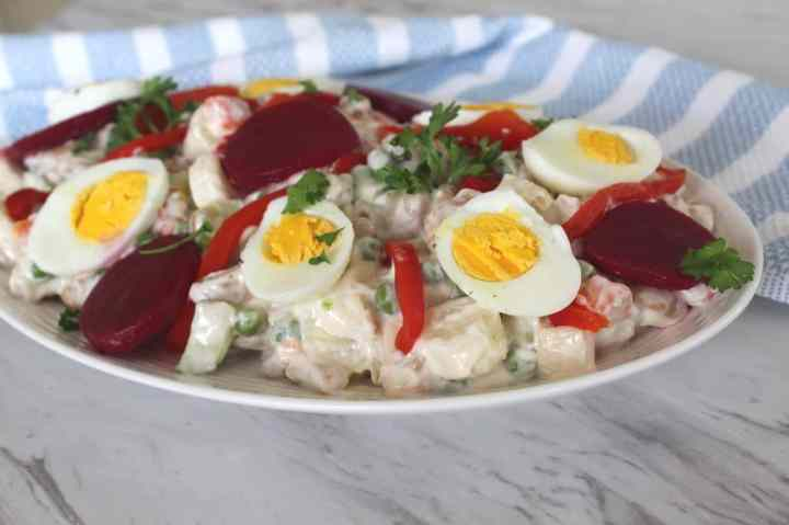 An oval plate with sallate ruse - Albanian version of the famous russian salad. Salad is garnished with boiled eggs, beets and roasted peppers.