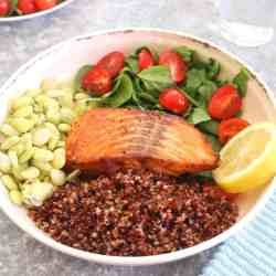Healthy Salmon Red Quinoa Dinner Bowl with green lima beans, spinach and grape tomatoes.