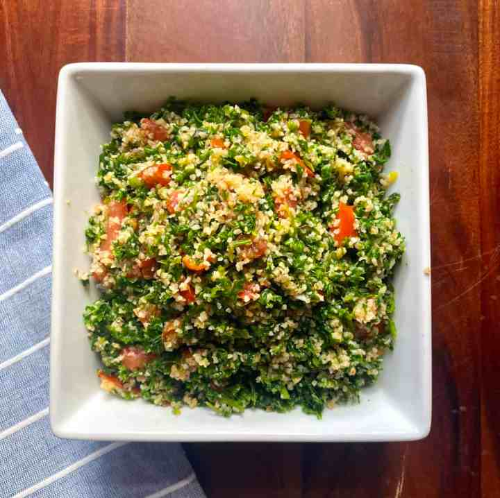 Tabouli salad chopped with an electrical food chopper. Salad is made with lots of parsley, mint, green onions, tomatoes, bulgur, lemon juice and olive oil.