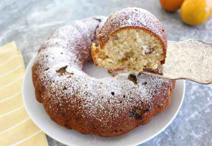 Orange bundt cake served in a white plate, shown with a slice being lifted with a silver spatula from the plate.
