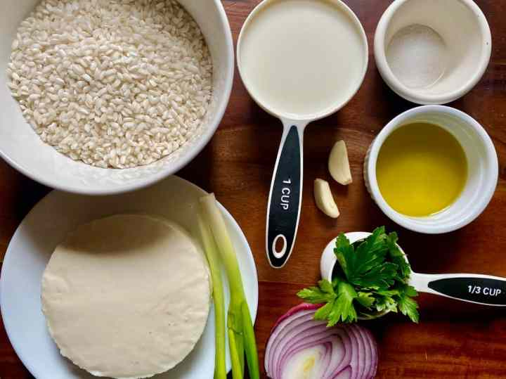Ingredients used to cook cheese rice: pearl rice, milk, salt, queso fresco, green onions, garlic, olive oil, cilantro and red onion.