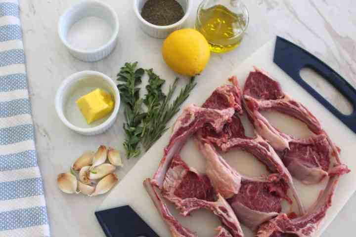 All the ingredients displayed for a visual understanding of what's needed for this recipe. Butter, fresh oregano, fresh rosemary, lemon, olive oil, garlic, lamb chops.