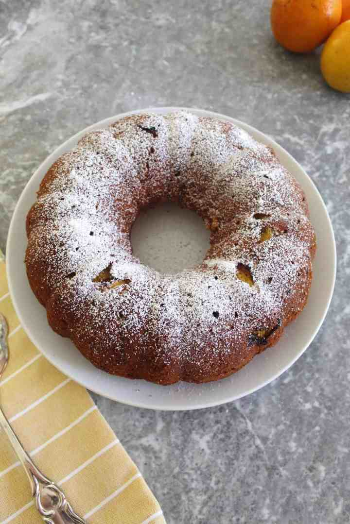 Orange bundt cake with walnuts shown on a white plate, sprinkled with confectioner's sugar.
