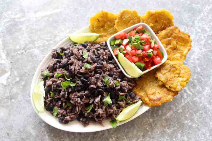 A platter with rice and black beans, pico de gallo, lime wedges and tostones.
