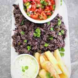 Rice & Black beans family style dinner served in a platter with a tomato based salad and fried yucca with a dip.